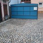 Pflasterarbeiten und blaues Tor
